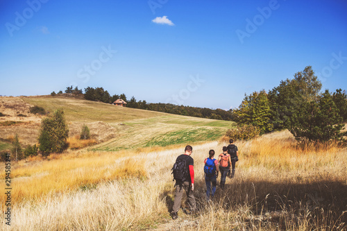 Fotomural Rear view of unrecognizable people with backpack hiking in the nature