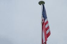 USA Flag On A Flagpole With Gray Sky, With Space