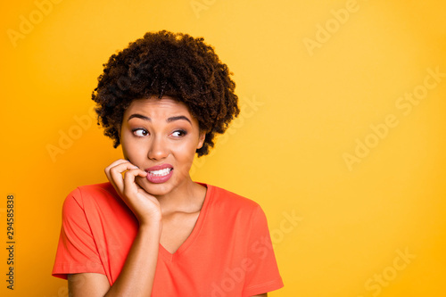 Fototapeta Copyspace photo of frightened afraid fearful woman biting her nails while observing terrible stuff going on wearing orange t-shirt isolated over yellow vivid color background obraz