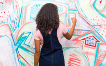 Young Pretty African American Woman Standing And Pointing To Object On Copy Space, Rear View Against Graffiti Wall