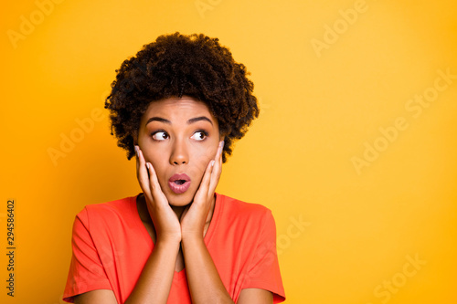 Fototapeta Photo of black afro american fearful girlfriend feeling guilty about something holding her cheeks with hands lips pouted isolated over yellow vibrant color background obraz na płótnie