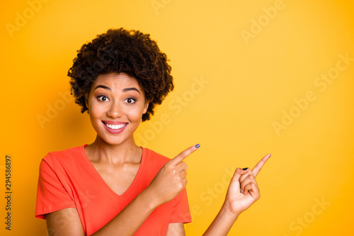 Phoo of curly wavy cheerful cute charming fascinating girlfriend pointing at emptiness with her forefingers smiling toothily wearing orange t-shirt isolated over vivid color yellow background