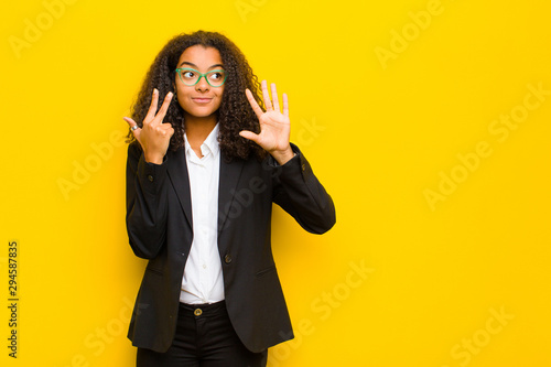 Fotografía  black business woman smiling and looking friendly, showing number eight or eight