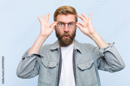 young blonde adult man feeling shocked, amazed and surprised, holding glasses wi Wallpaper Mural