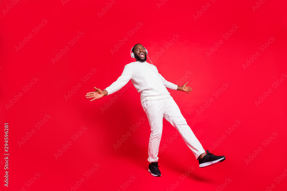 Fototapety, obrazy: Full length photo of amazing dark skin man listening favorite playlist in earflaps enjoy best moment moving with rhythm wear knitted sweater and trousers isolated red background