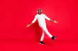 canvas print picture - Full body photo of amazing dark skin man listening favorite playlist in earflaps moving with rhythm down street wear knitted sweater trousers isolated red background