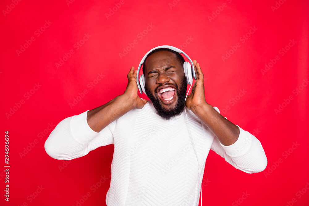 Fototapety, obrazy: Photo of funny dark skin man listening to favorite playlist in earflaps crazy singing cool track wear white knitted sweater isolated red background
