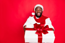 Portrait Of Positive Brown Hair Afro American Man In Santa Claus Cap Feel Festive Enjoy Xmas Christmas Celebration Tradition Give Big Gift Box Wear White Sweater Scarf Isolated Over Red Color