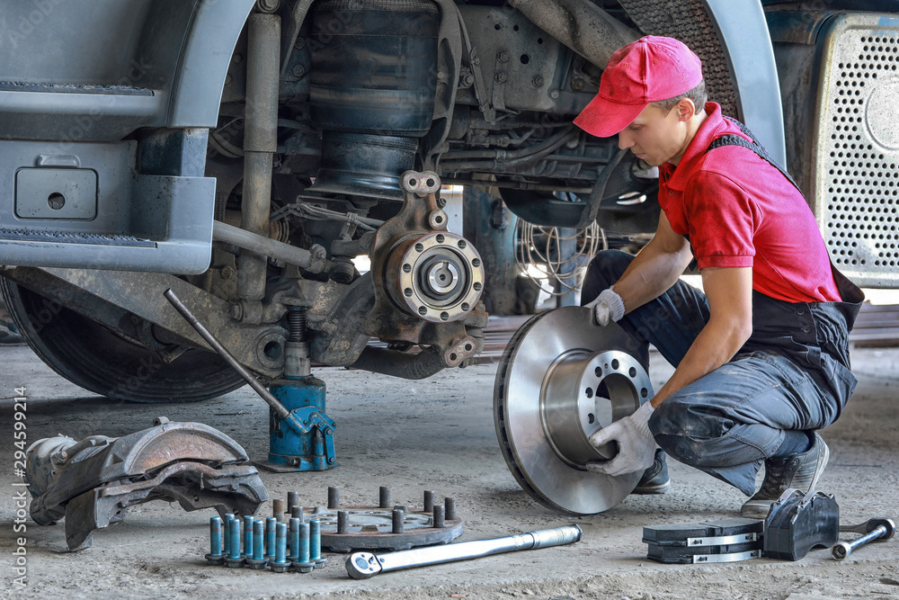 Fototapety, obrazy: A mechanic repairs a truck. Replace brake disc and pads