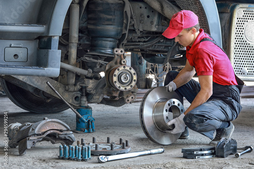 mata magnetyczna A mechanic repairs a truck. Replace brake disc and pads