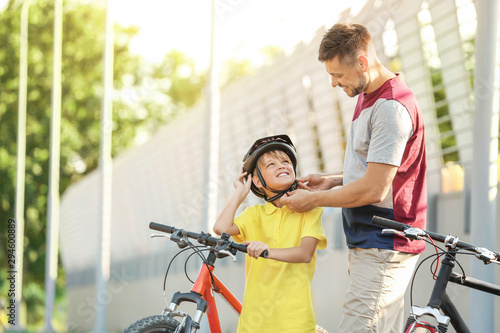 Father helping his son to put on bicycle helmet outdoors