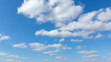 Fluffy White Cumulus Clouds In The Blue Sky On A Sunny Day