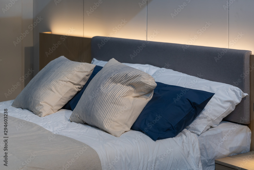 Fototapety, obrazy: Modern white, blue, brown fabric pillows with brown fabric headboard on the bed interior decoration
