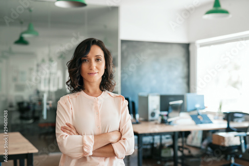 Confident young businesswoman standing with her arms crossed at work