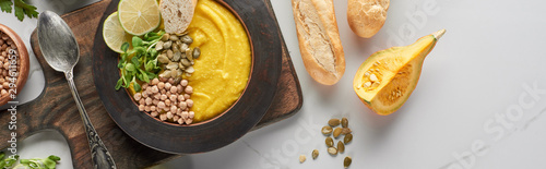 top view of autumnal mashed pumpkin soup in bowl on wooden cutting board on marble surface, panoramic shot