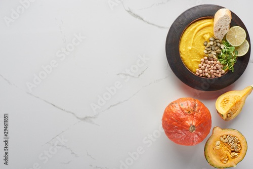 top view of autumnal mashed pumpkin soup in bowl near pumpkin on marble surface