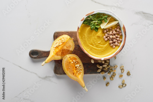 top view of autumnal mashed pumpkin soup in bowl on wooden cutting board near pumpkin, seeds on marble surface