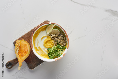 top view of autumnal mashed pumpkin soup in bowl on wooden cutting board with pumpkin on marble surface