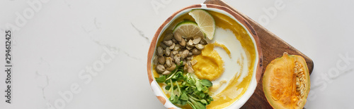 top view of autumnal mashed pumpkin soup in bowl on wooden cutting board with pumpkin on marble surface, panoramic shot