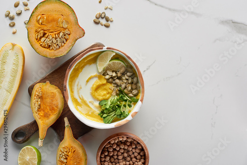 top view of autumnal mashed pumpkin soup in bowl on wooden cutting board near pumpkin, lime and chickpea on marble surface