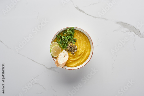 top view of tasty mashed pumpkin soup on marble surface