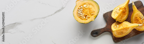 top view of cut pumpkin on wooden cutting board on marble surface, panoramic shot