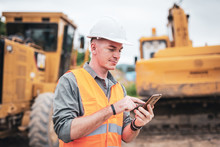 Portrait Of Caucasian Engineers Use Smartphones In The Workplace. Road Construction Site