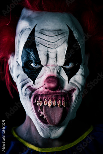 scary evil clown sticking out his tongue Fotobehang