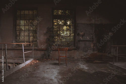 Wooden chair in front of an old and broken window within an abandoned building Wallpaper Mural