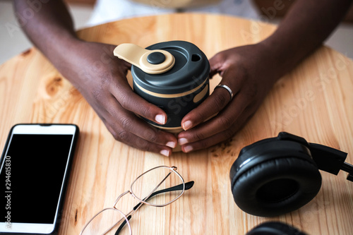 Fotografie, Obraz  Young black girl listening to music on smartphone at cafe.
