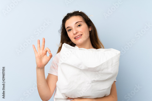 Fototapeta Young woman in pajamas over isolated blue background showing ok sign with fingers obraz na płótnie