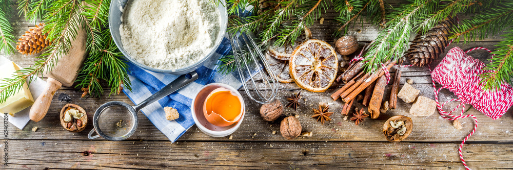 Fototapety, obrazy: Christmas baking background with utensils and ingredients - flour, eggs, brown sugar and spices. With christmas decorations and fir tree on rustic wooden background, top view with copy space.