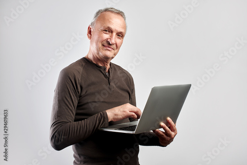 Photo sur Toile Ecole de Danse Stylish elderly man with laptop in hands pays for services and buys goods over the Internet with home delivery isolated on white background, online store