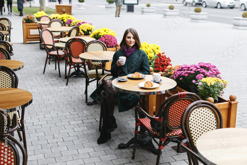 Obraz Beautiful young girl wearing green coat sitting at a table in cozy street outdoor cafe and drinking coffee with a croissant. Restaurant terrace is decorated with chrysanthemum flowers bushes in autumn - fototapety do salonu