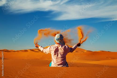 Single Man throws sand in the Sahara desert at sunset. Fototapet