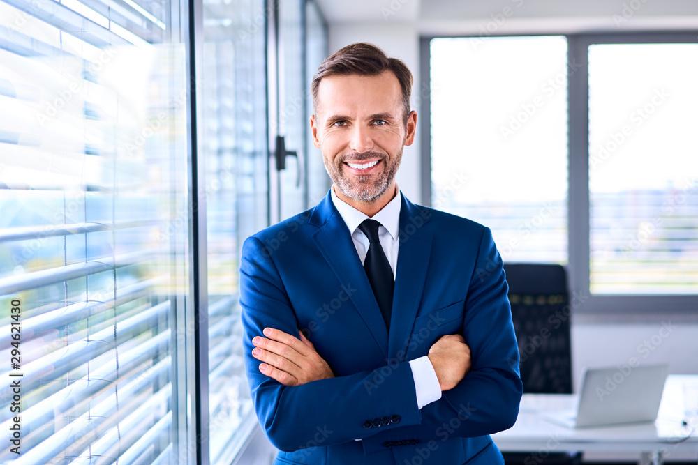 Fototapeta Portrait of successful businessman standing in corner office