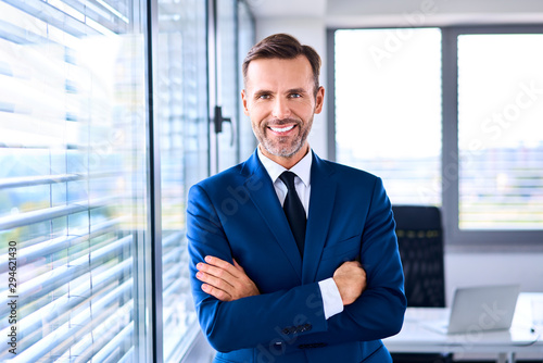 Portrait of successful businessman standing in corner office Fotobehang