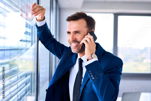 Fotografía Happy successful businessman in office talking on the phone
