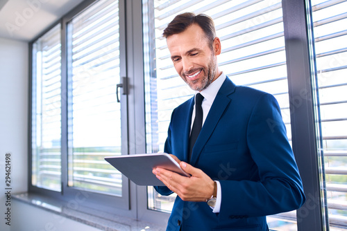 Fototapety, obrazy: Happy businessman standing with tablet in office