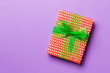 canvas print picture - wrapped Christmas or other holiday handmade present in paper with green ribbon on purple background. Present box, decoration of gift on colored table, top view with copy space