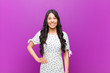 canvas print picture - young pretty latin woman smiling happily with a hand on hip and confident, positive, proud and friendly attitude against purple wall