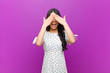 canvas print picture - young pretty latin woman smiling and feeling happy, covering eyes with both hands and waiting for unbelievable surprise against purple wall