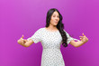 canvas print picture - young pretty latin woman looking proud, arrogant, happy, surprised and satisfied, pointing to self, feeling like a winner against purple wall