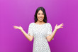 canvas print picture - young pretty latin woman feeling happy, excited, surprised or shocked, smiling and astonished at something unbelievable against purple wall