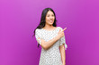 canvas print picture - young pretty latin woman smiling cheerfully, feeling happy and pointing to the side and upwards, showing object in copy space against purple wall