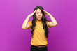 canvas print picture - young pretty latin woman looking stressed and frustrated, working under pressure with a headache and troubled with problems against purple wall