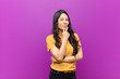 canvas print picture - young pretty latin woman looking serious, confused, uncertain and thoughtful, doubting among options or choices against purple wall