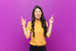 canvas print picture - young pretty latin woman smiling and anxiously crossing both fingers, feeling worried and wishing or hoping for good luck against purple wall