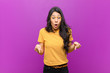 canvas print picture - young pretty latin woman feeling shocked, open-mouthed and amazed, looking and pointing downwards in disbelief and surprise against purple wall