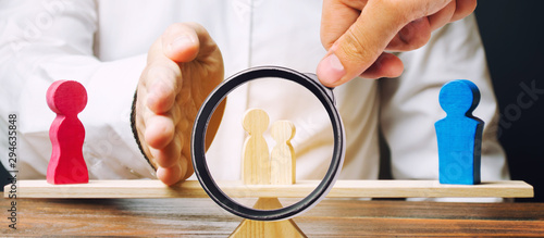 A magnifying glass looks at a man with a palm separates children from mother to father Fototapet